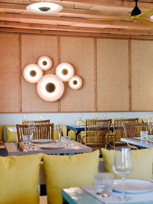Inside seating area with authentic Ibizan wooden ceiling, colourfully tiled tables and cosy yellow cushions.