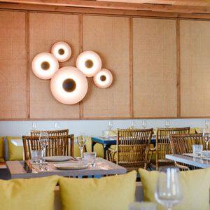 Zona de asientos interior con auténtico techo de madera ibicenco, mesas de azulejos de colores y acogedores cojines amarillos.