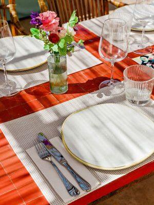 Detalle de una mesa de azulejos rojos muy bien puesta, con decoraciones florales e ilustraciones mediterráneas en los menús.