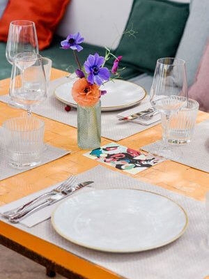 Detail of a beautifully laid orange tiled table with floral decorations and Mediterranean illustrations on the menus.