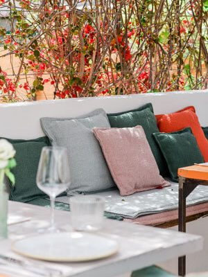 Shady restaurant terrace with a flower rooftop, cosy stone bench with many colourful cushions and set tables.