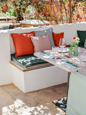 La terraza del restaurante es sombreada, con un tejado de flores, un acogedor banco de piedra con muchos cojines de colores y mesas puestas.