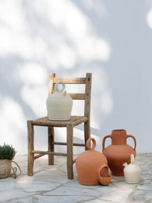 Different authentic local ceramic artworks infront of a white ibizan house