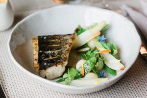 White ceramic plate with grilled grouper with snow peas and sauted onions.
