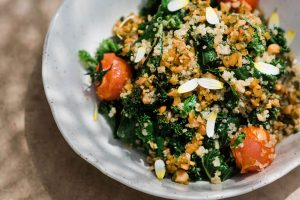 White ceramic plate showing the grilled kale salad with quinoa and cherry tomato confit.