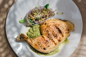 White ceramic plate with grilled local farmhouse chicken with broccoli and chimichurri from green tomatoes.